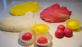 在三种颜色的面团球和曲奇饼由面团制成 库存图片