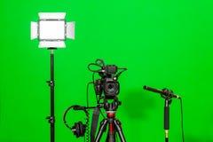在三脚架、被带领的泛光灯、耳机和一台定向传声器的照相机在绿色背景 色度钥匙 免版税库存照片