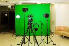 在三脚架、被带领的泛光灯、耳机和一台定向传声器的照相机在绿色背景 色度钥匙 库存照片