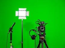 在三脚架、被带领的泛光灯、耳机和一台定向传声器的照相机在绿色背景 色度钥匙 图库摄影