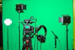 在三脚架、被带领的泛光灯、耳机和一台定向传声器的照相机在绿色背景 色度钥匙 免版税库存图片
