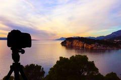 在三脚架有海洋的和日落的照相机在背景/克罗地亚中 免版税图库摄影