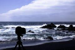 在三脚架有海洋的和黑海滩的照相机在背景中 免版税库存图片