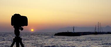 在三脚架有海的和日落的照相机在背景中 图库摄影