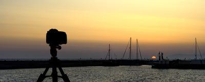 在三脚架有海的和日落的照相机在背景中 库存照片