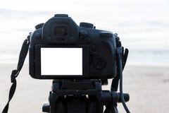 在三脚架白色屏幕上的数字照相机在海滩 库存照片