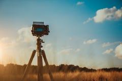 在三脚架的照相机在麦田,在日落天空的剪影与whie移动的云彩在背景中 库存照片