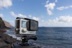 在三脚架的Gopro英雄4黑的行动照相机在海洋 免版税图库摄影
