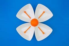 在三角陶瓷碗的橙色高尔夫球 免版税库存照片