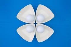 在三角陶瓷碗的白色高尔夫球 库存照片