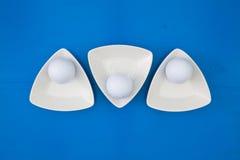 在三角陶瓷碗的白色高尔夫球 免版税库存照片