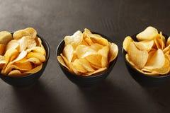 在三黑碗的嘎吱咬嚼的快餐在黑褐色背景 图库摄影