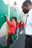 在上升的墙壁上的孩子在Breaktime的学校操场 库存照片