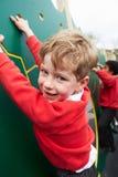 在上升的墙壁上的男孩在Breaktime的学校操场 库存照片