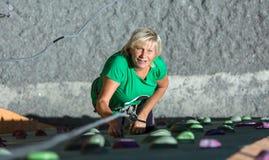 在上升的墙壁上的相当年迈的女运动员 免版税库存照片