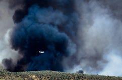 在上升从漫延的野火的密集的黑烟前的白色航空器飞行 库存图片