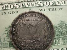 在上帝我们在钞票和摩根美元硬币信任 库存图片