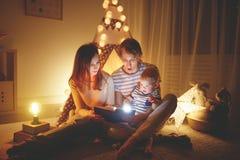 在上床时间前的愉快的家庭 母亲和父亲读了书给她 免版税图库摄影