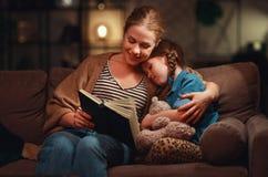在上床的母亲前的家庭读对她的儿童女儿书在一盏灯附近在晚上 免版税库存图片