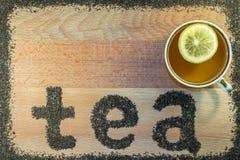 在上是一个杯子茶 在有切片的一个杯子柠檬 在委员会张贴词茶的信件 免版税库存图片
