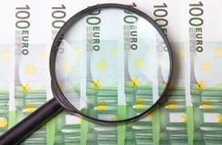 在上百张欧洲钞票的放大镜 库存图片