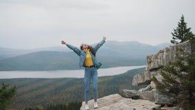 在上面的妇女游人是愉快和庆祝成功 牛仔布夹克的一名妇女在a幸福到极点高兴 股票视频