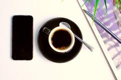 在上面的工作场所用咖啡和电话 免版税库存照片