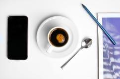 在上面的工作场所用咖啡和电话 免版税图库摄影