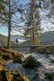 在上面的瀑布风景与桥梁树和远足人的妇女景色在有岩石和青苔的背景雾风景河 免版税库存图片