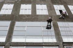 在上面的窗式洗衣机 在高层的两个工作者垂悬的绳索洗涤窗口 免版税库存照片