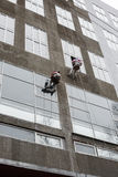 在上面的窗式洗衣机 在高层的两个工作者垂悬的绳索洗涤窗口 免版税库存图片