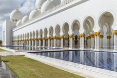 在上面的装饰的大理石柱与象有被反射的水池的金黄棕榈在扎耶德Grand Mosque回教族长前面早晨 免版税库存图片