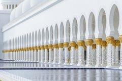 在上面的装饰的大理石柱与象有被反射的水池的金黄棕榈没有在扎耶德Grand Mosque回教族长前面的人 免版税图库摄影