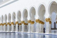 在上面的装饰的大理石柱与象有被反射的水池的金黄棕榈没有在扎耶德Grand Mosque回教族长前面的人 库存照片