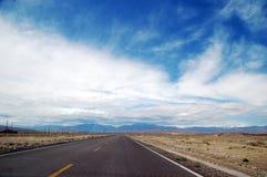 在下天空附近的蓝色沙漠高速公路 库存照片