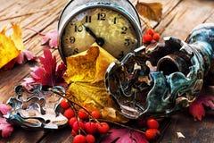 在下落的叶子背景的时钟  免版税库存照片