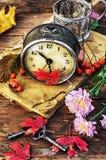在下落的叶子背景的时钟  免版税库存图片