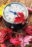 在下落的叶子背景的老时钟  免版税图库摄影