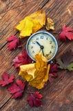 在下落的叶子背景的老时钟  图库摄影