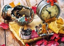 在下落的叶子背景的老时钟  免版税库存图片