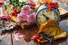 在下落的叶子背景的老时钟  免版税库存照片