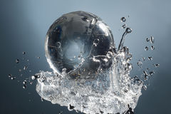 在下落水飞溅的玻璃地球行星在蓝色背景 免版税图库摄影