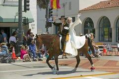 在下降状态营业日游行街道,圣塔巴巴拉,加州,老Spani期间,新娘和新郎用西班牙语成套装备一起骑乘马 免版税库存图片