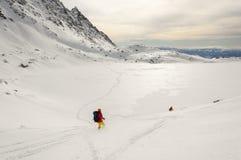 在下降狂放的倾斜期间的滑雪者 免版税图库摄影