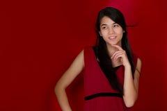 在下巴认为的美好的两种人种的青少年的女孩手 红色backgrou 库存照片
