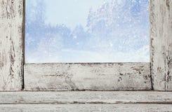 在不可思议的冬天风景前面的老窗口基石 图库摄影