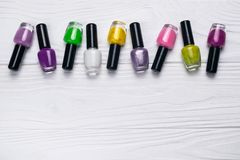 在不同颜色的指甲油瓶在白色木背景 免版税库存照片