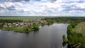 在不尽的领域包围的小村庄附近的河分裂 股票视频