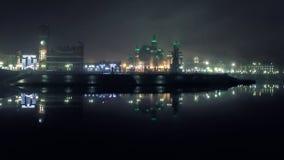 在不祥的雾的光照亮的夜城市的塔和城堡在冷的河对称地被反射 库存图片