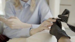 在不育的手套的修指甲大师做修指甲给有电话的妇女 影视素材